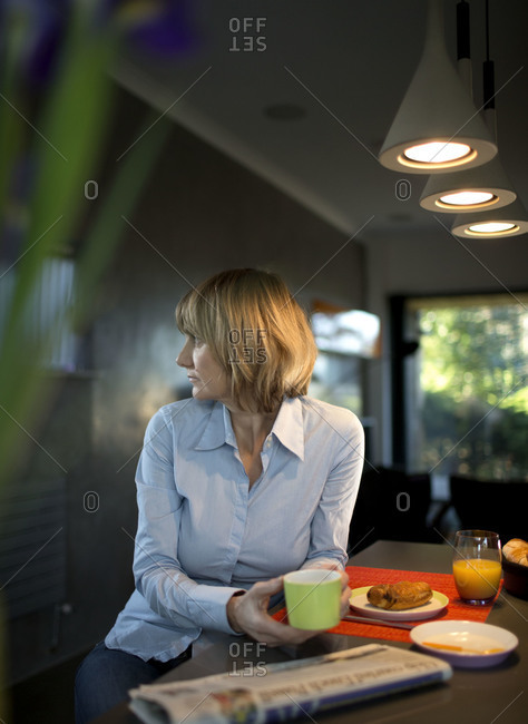 Woman at breakfast table staring off