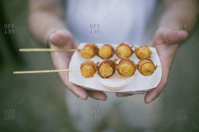 A man holds a tray of bacon wrapped tater tots