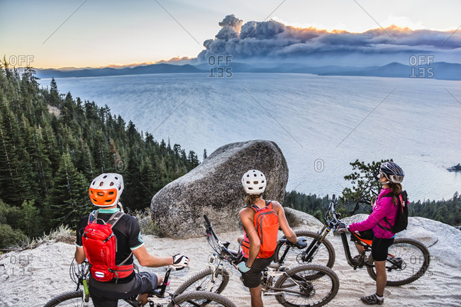 Three mountain bikers are resting on the Flume Trail