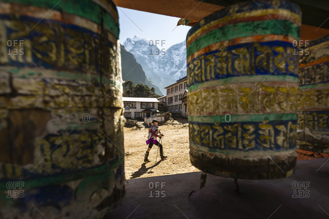 Khumbu region, Nepal - December 9, 2012: A woman is hiking passes a prayer wheels at Tengboche Monastery