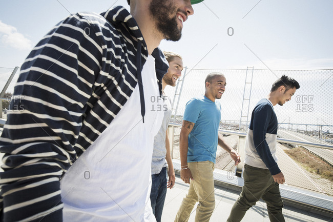 Group of young men walking along a bridge