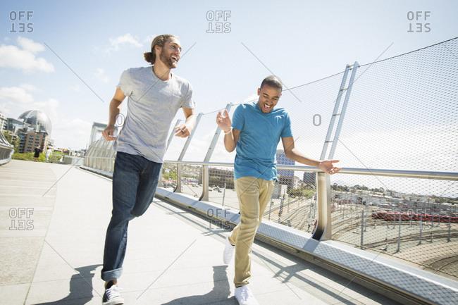 Two young men jogging along a bridge