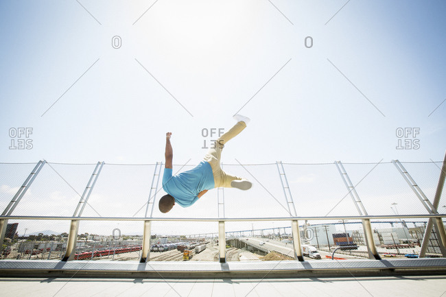 Young man somersaulting on a bridge