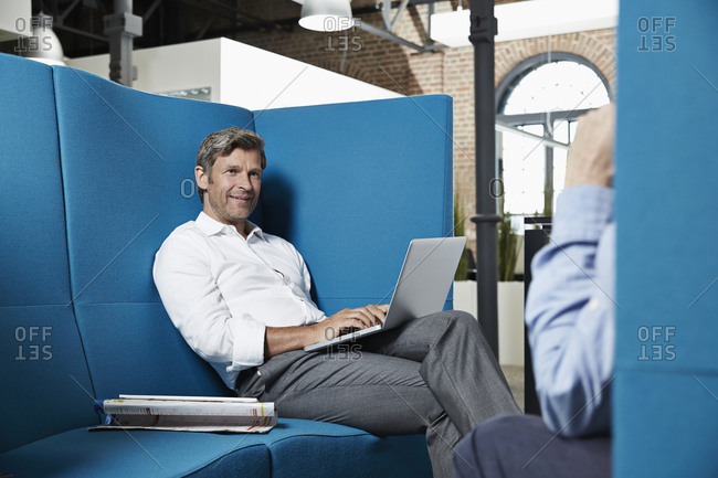 Businessman sitting in conversation pit in office looking at colleague