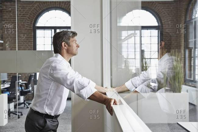 Businessman in office standing at glass pane