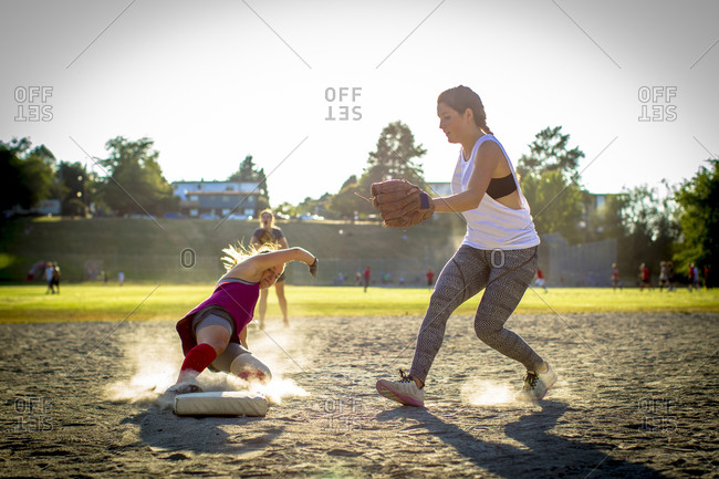 Softball player sliding into base in Vancouver, Canada