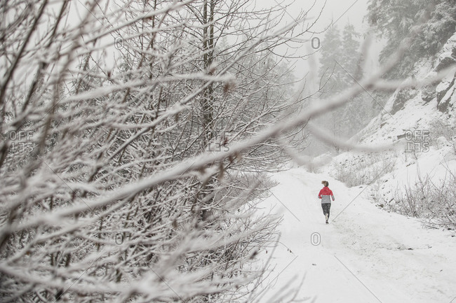 Woman running in the snow on a trail