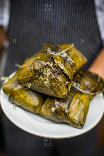 Chef holding plate of Colombian tamales wrapped in plaintain leaves