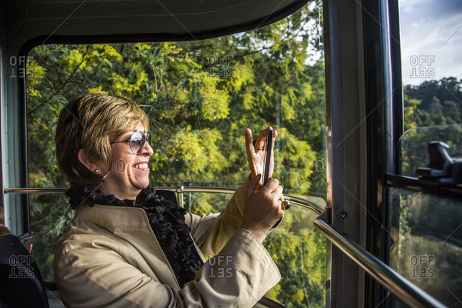 Colombia, Bogota - December 4, 2013: Woman riding cable car up Bogota mountain takes photo with smartphone