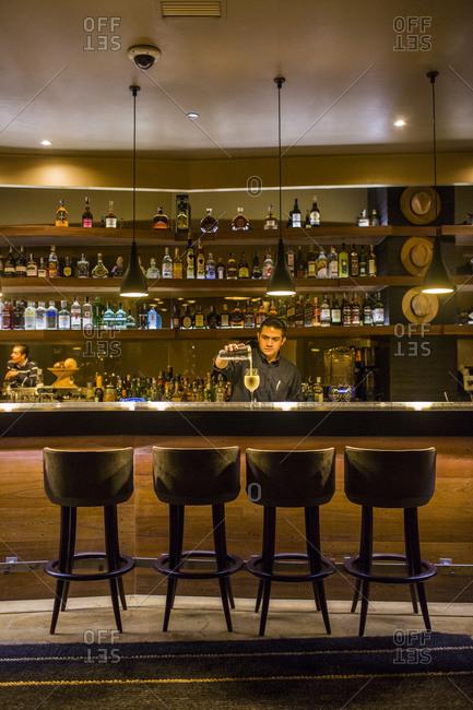 Bogota, Colombia - December 4, 2013: Bartender pours drink at bar
