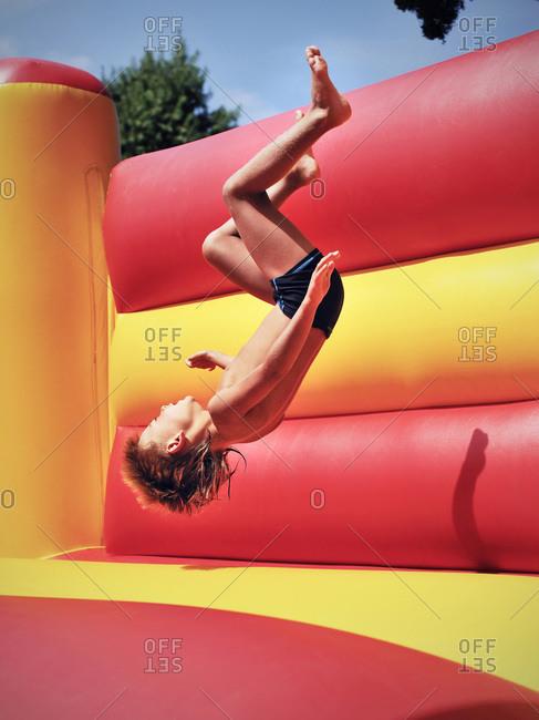 Aalen, Germany - August 7, 2009: Young boy flips in bouncy castle