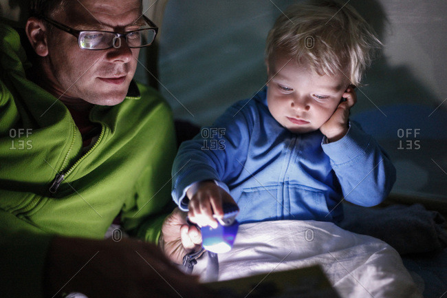 Father reading his son a bedtime story in a tent