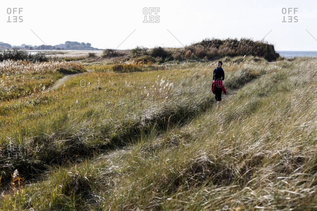 Mecklenburg-West Pomerania, Germany - October 19, 2012: Woman walking on a grassy coastal path in autumn next to the Baltic Sea