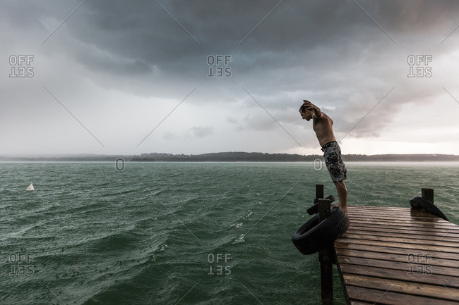 Young man leaning into the wind during a thunderstorm on a lake