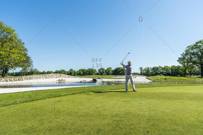 Golfer swinging club on the fairway