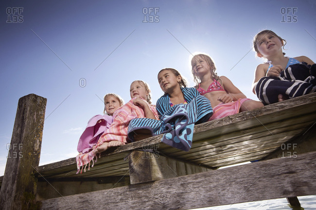 Five young girls wrapped in towels sitting on dock
