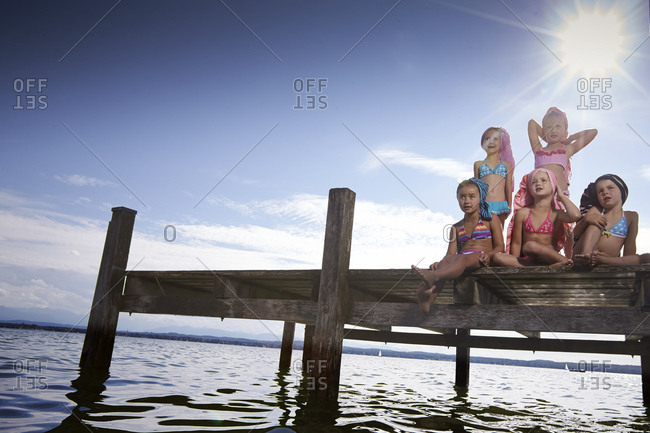 Five young girls posing on lakefront dock
