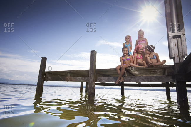 Five young girls sitting together on a lakefront dock