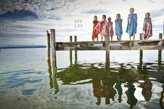 Six girls stand on dock wrapped in towels after swimming in lake
