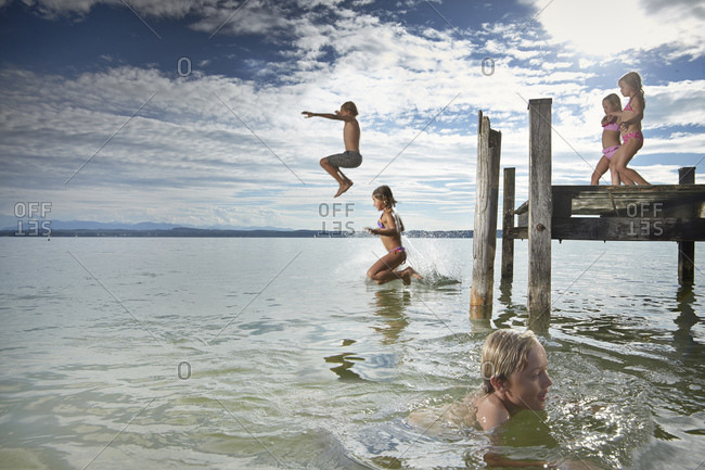 Children jumping off dock into lake