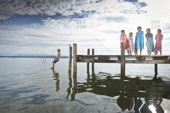 Girls watch as boy jumps off dock into lake