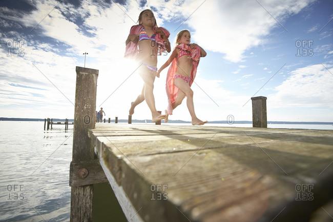 Children running on lakefront dock in summer
