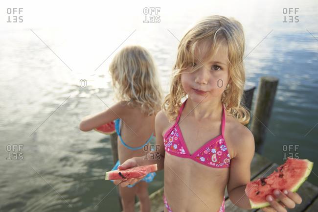 Two little girls eating watermelon on lakefront dock
