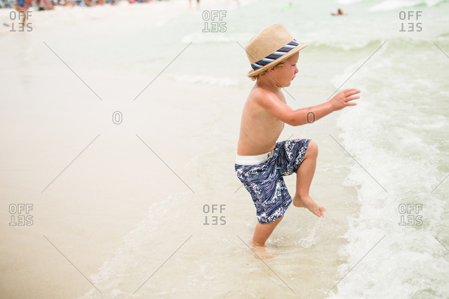 A little boy in a fedora plays in waves
