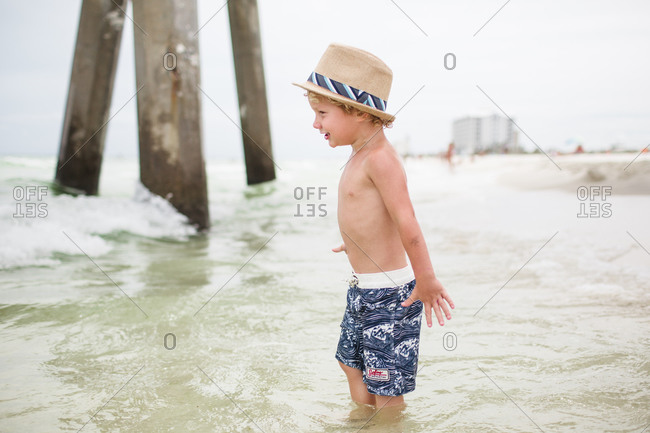 A little boy in a fedora smiles at the shore
