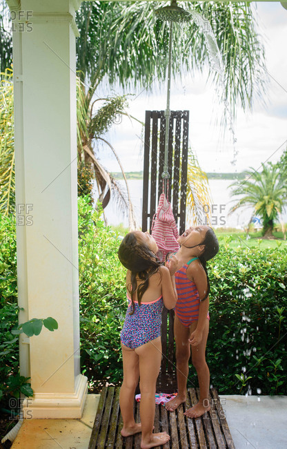 two girls drink water from an outdoor shower