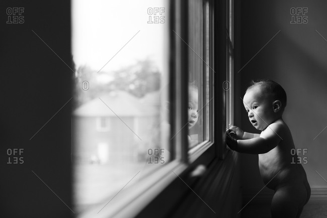 Little boy staring out of a window
