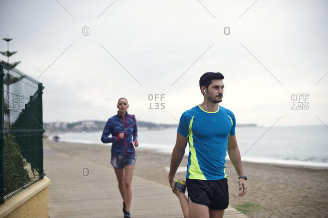 A man stretches on a boardwalk while a woman jogs behind him