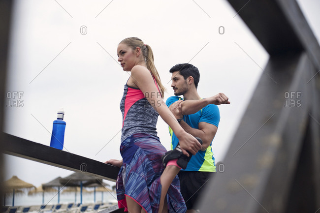A couple stretches on a boardwalk