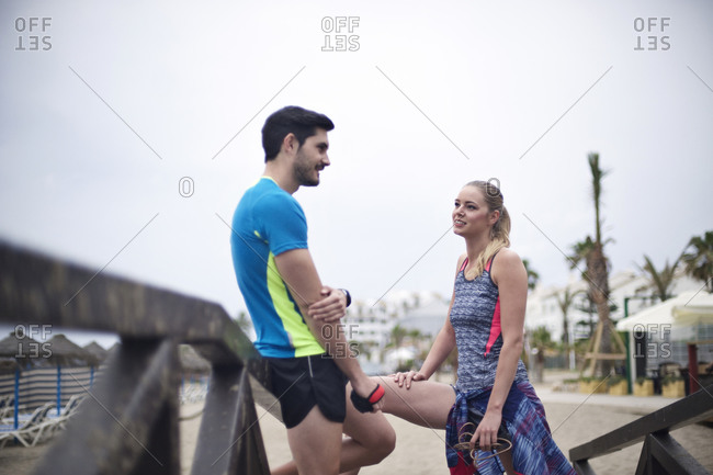 Joggers chat on a boardwalk