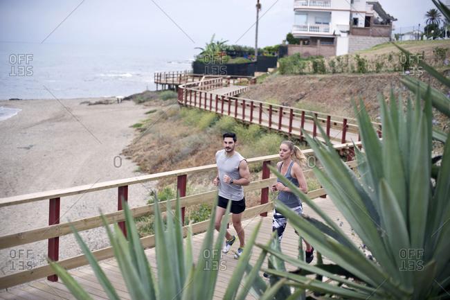 Joggers run along the seashore