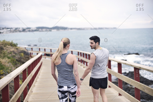 A pair of joggers stand on a boardwalk
