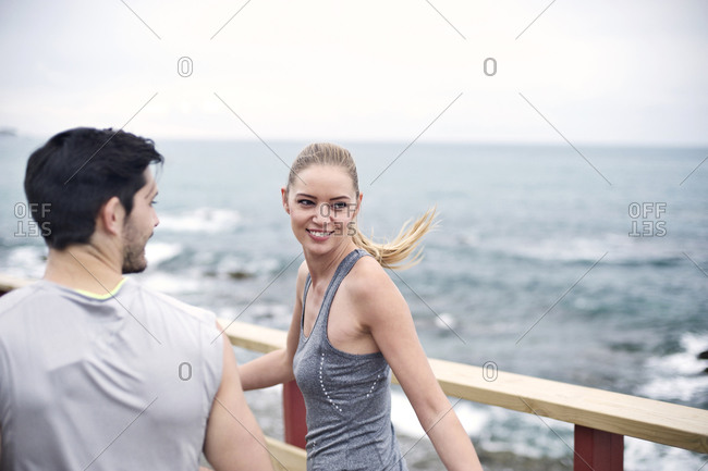 A woman with her jogging partner on a boardwalk