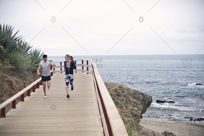 Joggers check the time while running at the beach