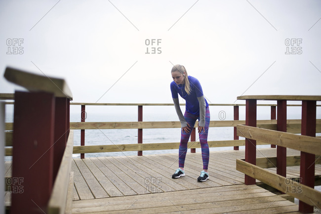 A jogger catches her breath on a boardwalk