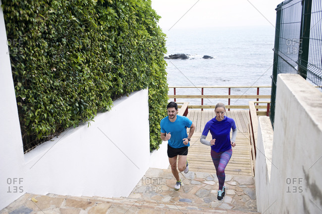 Joggers run up stairs by the beach