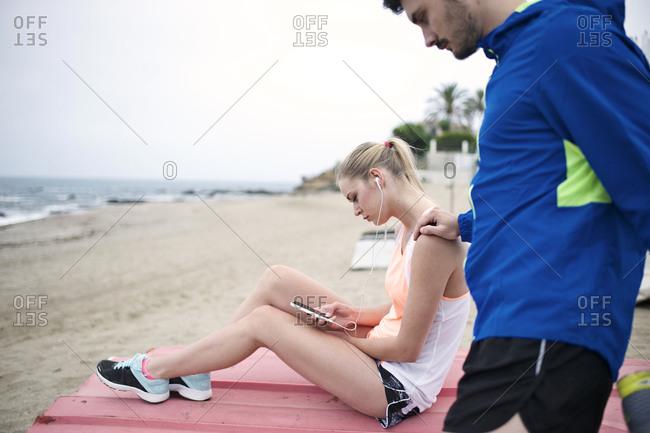 A couple prepares for a jog on the beach