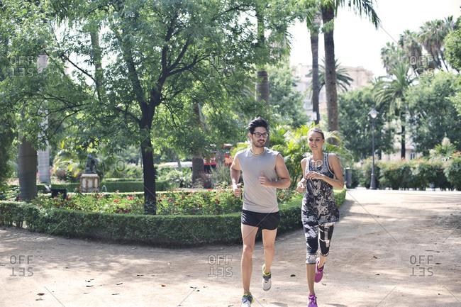 A couple jogs through a park