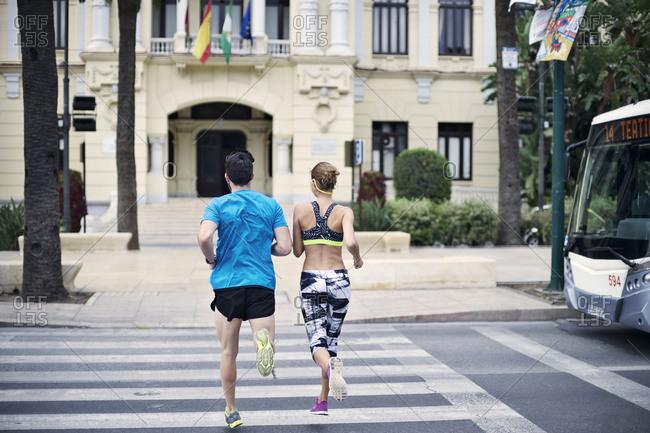 A couple jogs across a crosswalk