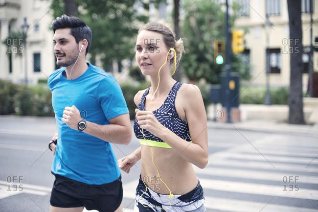 Joggers run across a crosswalk