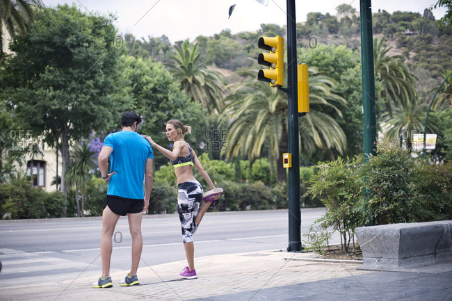 Joggers stretch and wait at a crosswalk