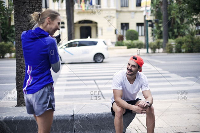 Two joggers chat at a crosswalk