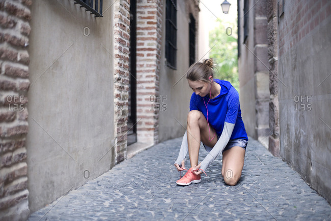 A jogger ties her shoe in an alley
