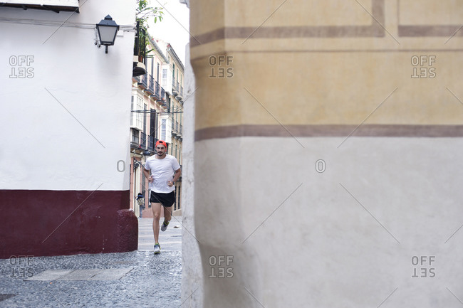 A man jogs down narrow city streets