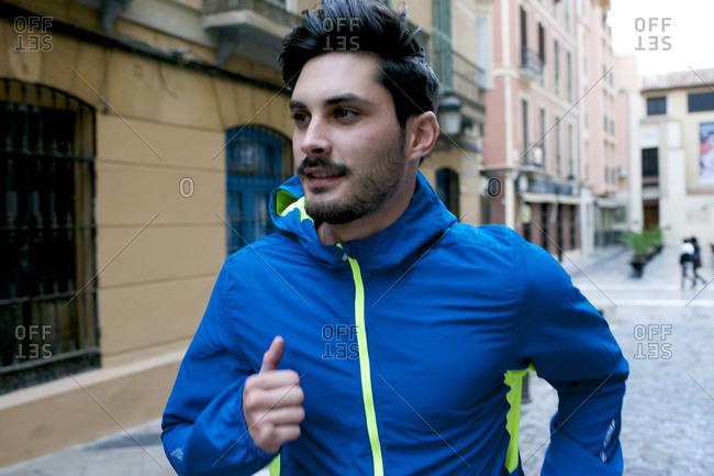 A man jogs down a city street