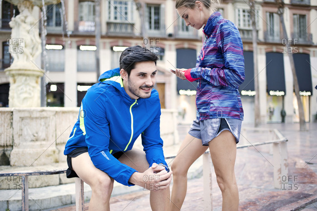 A couple prepares for a jog next to a fountain